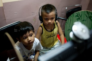 Two young boys surfing the internet and chatting online at an internet shop, Phnom Penh, Cambodia, Southeast Asia